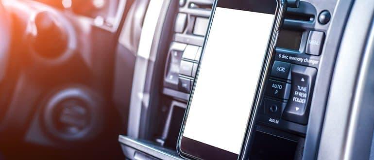 Smartphone vor einem Autoradio