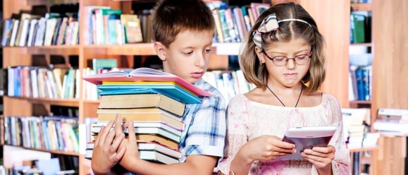 Ein Junge mit einem schweren Stapel Bücher und ein Mädchen beim E-Book-Reader-Test.