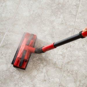 roter handdampfreiniger bei der Säuberung von Badezimmerfliesen