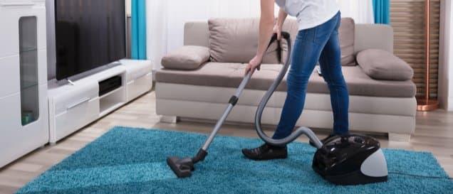 Mann saugt einen Teppich im Wohnzimmer