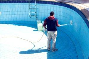 mann reinigt pool