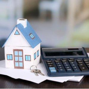 Haus und Taschenrechner auf Dokumenten zur Anschlussfinanzierung des Immobilienkredits
