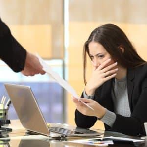Frau, die am Arbeitsplatz unrechtmäßig ihre Kündigung erhält und damit einer Arbeitsrechtsschutzversicherung bedarf