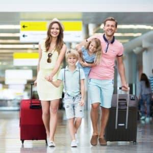junge Familie an Flughafen mit Koffern