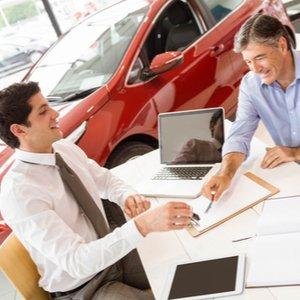 Junger Verkäufer und Mann, der Auto mit Autokredit kaufen möchte