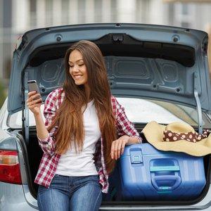 junge Studentin neben Auto, das sie sich dank Autokredit leisten kann