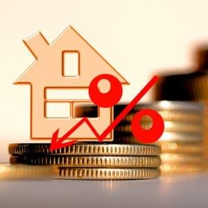 Münzen, Haus und Prozentzeichen, die sinkende Zinsen für Baufinanzierungen symbolisieren
