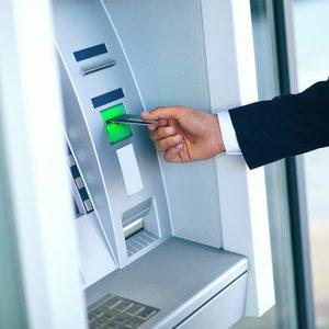 Mann, der an Geldautomat Geld von seinem Girokonto abheben möchte