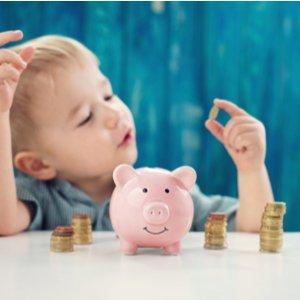 Kind, das vor Sparschwein sitzt und mit Münzen spielt