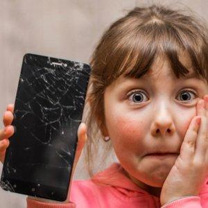 Kind, das kaputtes Handy in Hand hält, das durch Haftpflichtversicherung abgesichert ist