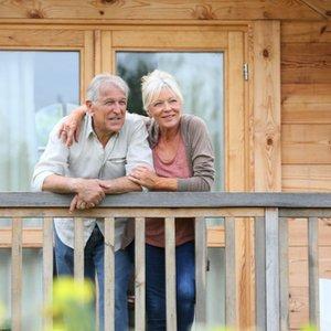 Älteres Ehepaar vor Ferienhaus, das sie sich dank Kapitallebensversicherung leisten können