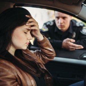Junge Frau, die von Polizist angehalten wird, aber dank KFZ Rechtsschutzversicherung mit Unterstützung rechnen kann