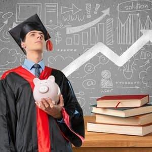 Student, der ein Kredit-Schwein in der Hand hält und neben Bücherstapel vor Tafel steht