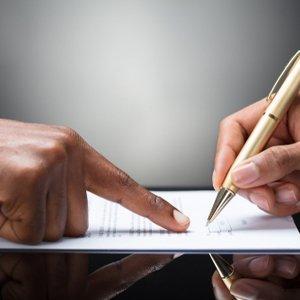 Zwei Hände, eine davon mit Kugelschreiber, die einen Kredit-Antrag berühren