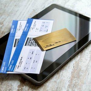 Gold Kreditkarte mit Reiserücktrittsversicherung auf Tablet und Flugtickets