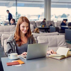 junge Frau, die dank Platin Kreditkarte mit Reiserücktrittsversicherung in VIP Lounge des Flughafens sitzt