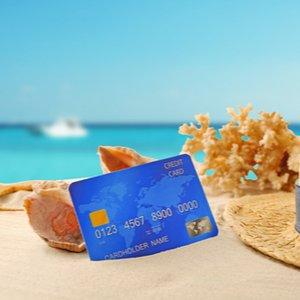 Kreditkarte, die in Sand am Meer steckt und von Muscheln umgeben ist