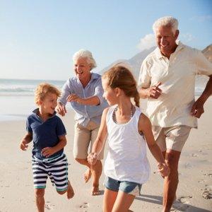 Senioren, die mit Enkeln dank privater Rentenversicherung im Urlaub Spaß haben