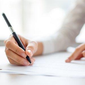 Frau, die mit Stift Dokumente zur Riester-Rente ausfüllt
