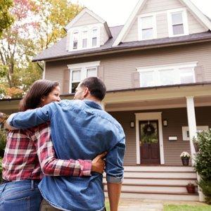 junges Paar vor Haus, dessen Finanzierung mit einer Risikolebensversicherung abgesichert wurde