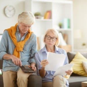 älteres Ehepaar, das gemeinsam Dokumente zur Rürup-Rente durchgeht