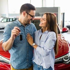 junges Paar, das mithilfe eines Sofortkredites Neuwagen gekauft hat