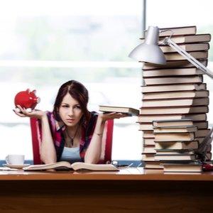 Junge Studentin zwischen Büchern, die Sparschwein in der Hand hält und über Studienkredit nachdenkt