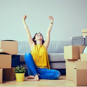 junge Frau, die dank Studienkredit ihre erste eigene Wohnung beziehen kann
