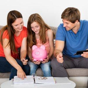 junges Mädchen, das mit Eltern ihr erstes eigenes Tagesgeld Konto bespricht