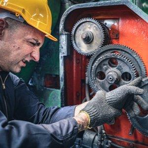 Mann, der sich Finger in einer Maschine klemmt, wobei er durch Unfallversicherung gegen finanzielle Schäden geschützt ist
