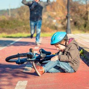 kleines Kind, das Unfall mit Fahrrad hatte, für dessen Folgen Unfallversicherung greift
